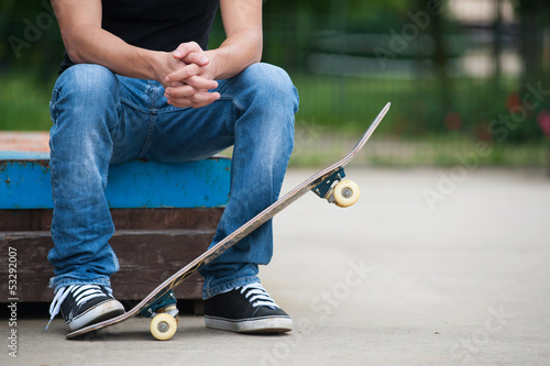 Man sit with skateboard.