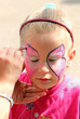 artist paints on face of little girl