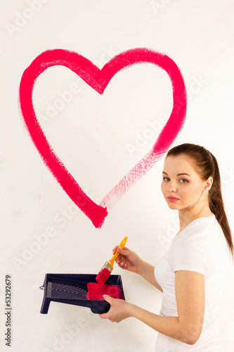 The girl in white t-shirt draws heart on white wall