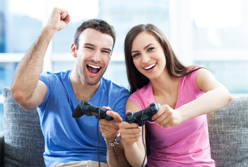 Excited couple playing video games on the sofa
