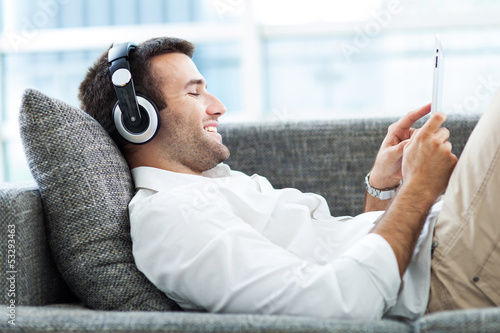 Man on sofa with headphones and digital tablet