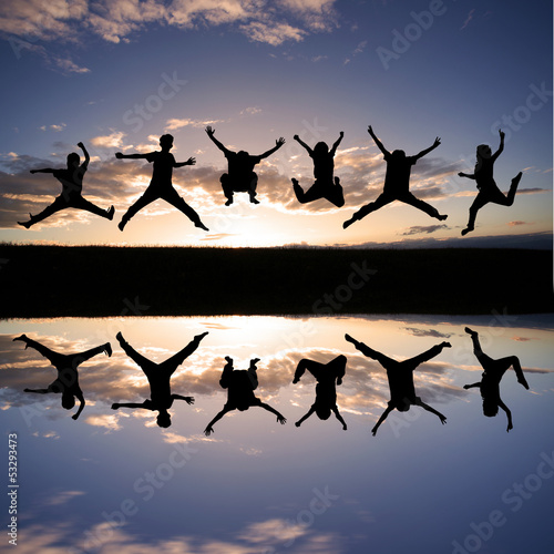 silhouette of kids jumping in sunset