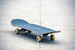 Old used skateboard isolated on the ground. Shallow dof.
