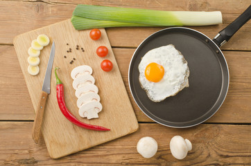 Fried egg in a frying pan on a wooden background