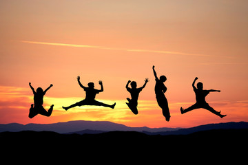 silhouette of kids jumping in sunset on hill