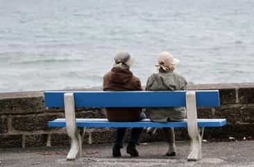 personnes âgées sur un banc face à la mer
