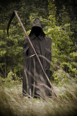 Death standing with scythe on hand