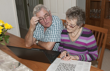 Elderly couple solving crossword puzzle