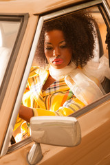 Retro 70s fashion african american woman driving in gold seventi