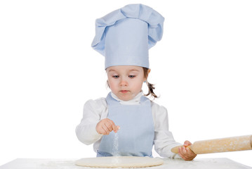 Beautiful little girl cooking  and sprinkle with flour pizza