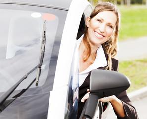 Lächelnde Frau im Elektroauto