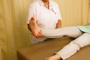 Physiotherapist treating quadriceps muscle