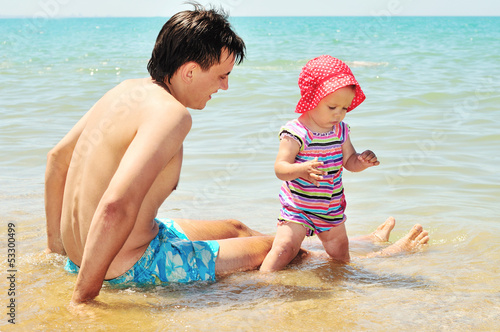 futher with baby on the beach