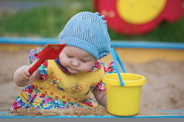 The little girl plays to a sandbox