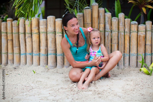 Young mother and two beautiful daughters sitting on the sand