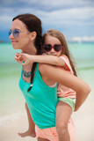 Young mother is riding her beloved daughter on the beach poster