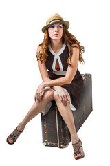 woman traveler sitting on retro suitcase