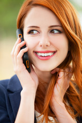 Redhead girl speaking by phone