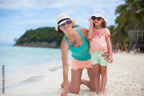 Young mother and her little daughter in hats have fun on beach