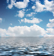 white clouds in the blue sky reflected in the water