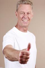 Aktiver älterer Mann hält lachend Daumen hoch