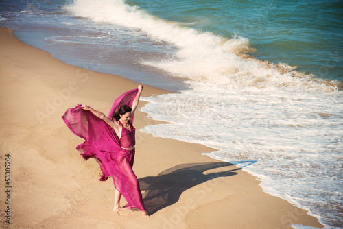 Woman in airy crimson dress dancing on the beach