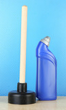 Toilet plunger and cleaner bottle on blue background