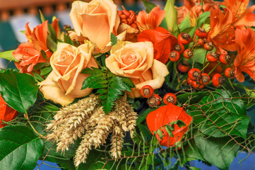 Herbstlicher Blumenstrauß mit Rosen, Hagebutten und Getreide