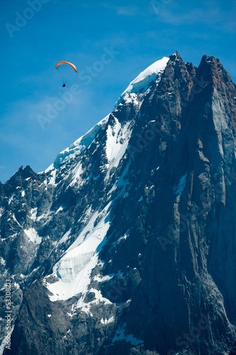 Red paraglide over Alps peaks