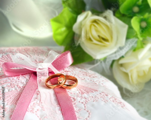 Wedding gold rings on a pillow with bouquet