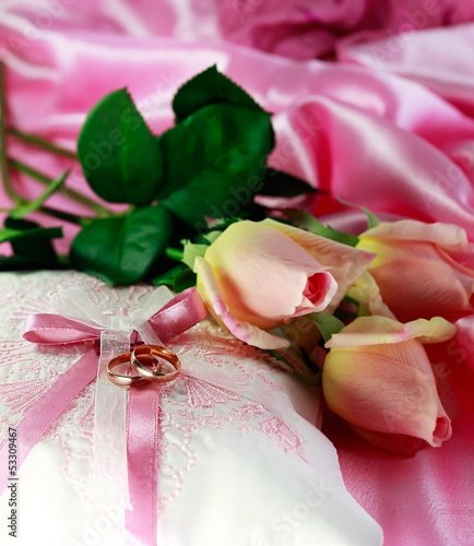 Wedding gold rings on a pillow with roses