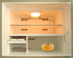 Yellow persimmon in an empty refrigerator