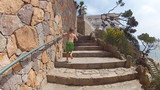 boy runs up the stairs along the seashore