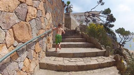 boy runs up the stairs along the seashore