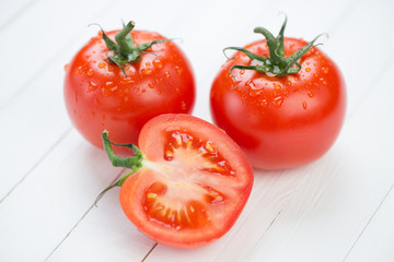 Two whole ripe tomatoes and one cut, horizontal shot