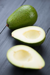 Avocado: one whole and one cut, vertical shot
