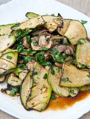 Slices of zucchini and mushrooms grilled in a sauce