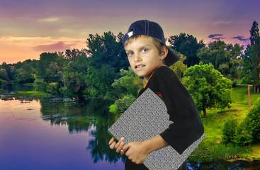 Мальчик с планшетом на фоне вечернего заката.