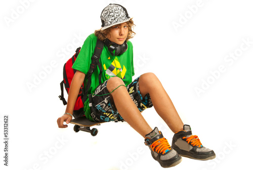 Schoolboy teen waiting on skateboard