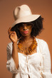Retro 70s fashion afro woman with sunglasses and white hat. Brow