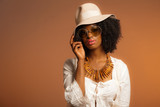 Retro 70s fashion afro woman with sunglasses and white hat. Brow poster