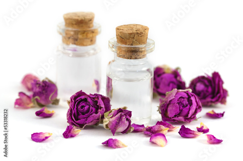 Two bottles filled with rose aroma oil and dried rose buds