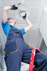 Janitor repairing broken lamp in office corridor