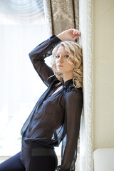 Portrait of pretty blonde in black chiffon blouse