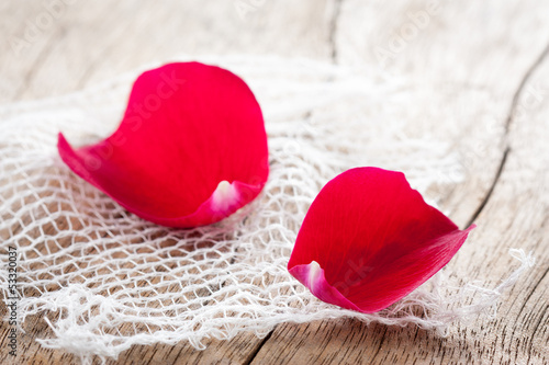 Two red rose petals on white cloth over wooden table