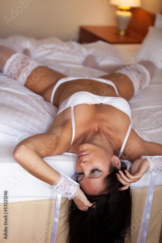 canvas print picture Frau in Dessous streckt sich im Hotelbett