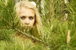 Beautiful blond woman behind a pine