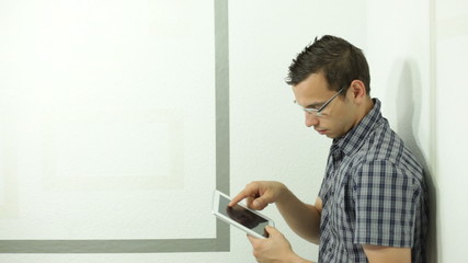 Young man leaning against wall and using tablet