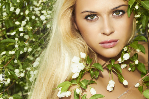 Beautiful blond woman with apple tree. flowers