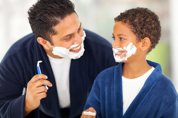 playful father and son shaving together